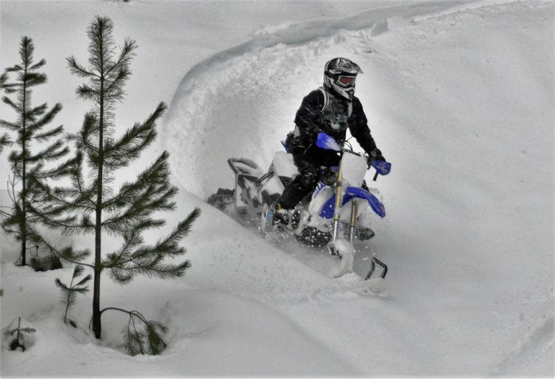Ryan Porter of Priest Lake Powersports rides his snow cycle off a slope above Priest Lake, Idaho. (Rich Landers / The Spokesman-Review)
