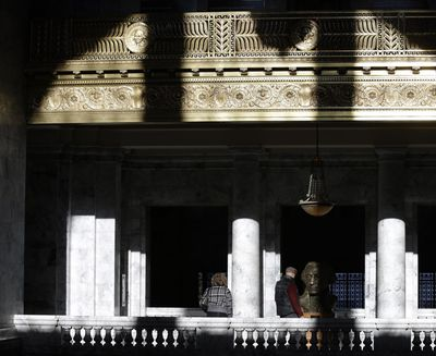 Midday sunlight streams through the rounded windows of the Capitol rotunda on Friday in Olympia as visitors view a bust of George Washington. (Associated Press)