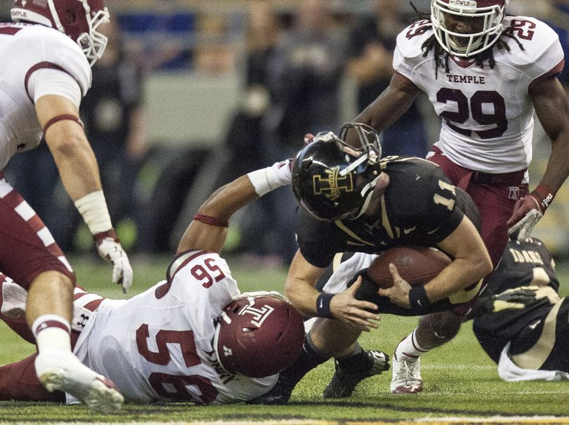 Idaho QB Chad Chalich gets his helmet spun around as he's brought down by Temple's Sharif Finch in the second quarter. (Associated Press)