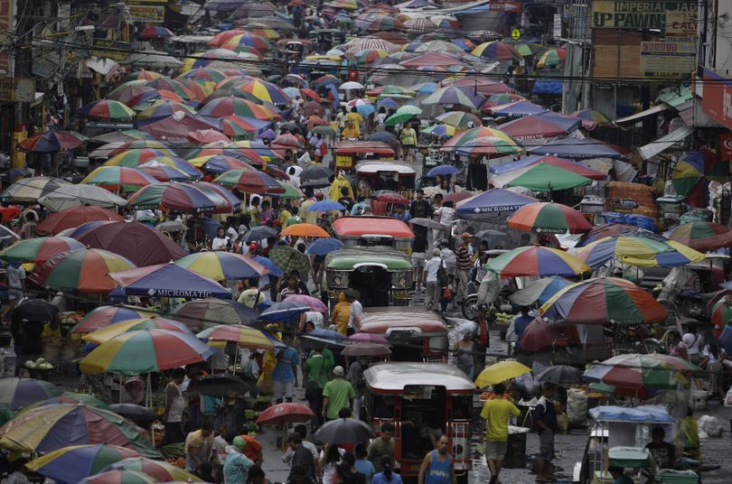 Passenger jeepneys make their way along a crowded public market as people and vendors cover themselves with umbrellas during a downfall in suburban Manila, Philippines on Wednesday June 8, 2011. Traffic snarled as the Philippine capital experienced a day of rain. (Aaron Favila / Associated Press)