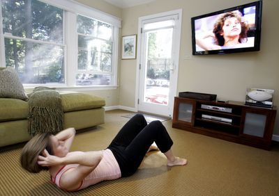Katie Feuer follows an exercise video at her home in Summit, N.J., earlier this month.  Feuer, 35, and a mother of two, does a 12-minute exercise tape most days of the week and says it helps keep her in shape.  (Associated Press / The Spokesman-Review)