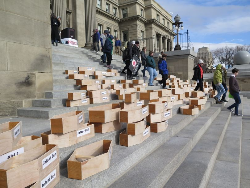 Protesters stacked 183 symbolic child-sized coffins on the Idaho Capitol steps on Monday, Feb. 19, 2018, calling for Idaho to repeal its faith-healing exemption, which allows parents to deny their children medical care without civil or criminal liability, even if the children die. (Betsy Z. Russell)