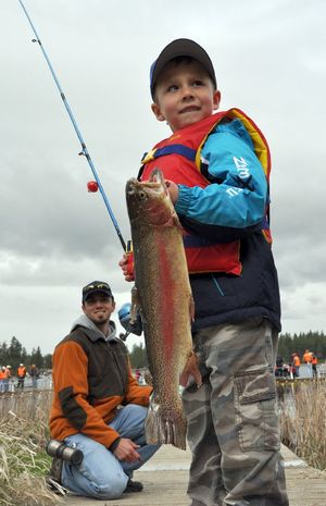 Carson Blakesley of Post Falls caught one of the few really big rainbows swimming with the more average-sized trout in the net pens set up at Clear Lake for the annual Kids Fish-In on May 1. Colby Price, in the background, caught a big one, too. Both boys are 5 years old. RICH LANDERS richl@spokesman.com