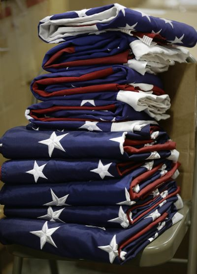 A stack of completed United States flags waits to be packaged. Today is the last day to vote in Washington's primary election. (Gerry Broome / AP)