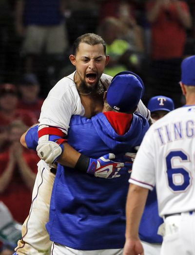 Texas' Rougned Odor celebrates with manager Jeff Banister, bottom, after Odor hit a two-run homer in the bottom of the ninth inning to defeat Seattle on Tuesday. (Tony Gutierrez / Associated Press)