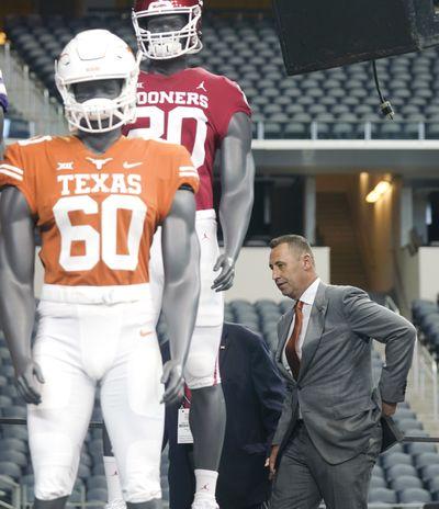 Texas head coach Steve Sarkisian walks on stage behind mannequins wearing Texas and Oklahoma uniforms during the NCAA college football Big 12 media days Thursday, July 15, 2021, in Arlington, Texas.  (Associated Press)