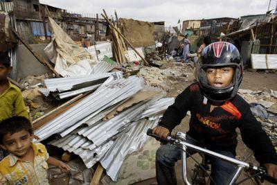 """Slumdog Millionaire"" star Azharuddin Mohammed Ismail  rides past bulldozed homes  in his Mumbai, India, shantytown  Thursday.  (Associated Press / The Spokesman-Review)"
