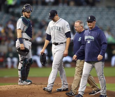 Seattle Mariners pitcher James Paxton, second from left, is escorted off the field after being hit by a ball in the first inning of a baseball game against the Oakland Athletics Tuesday, Aug. 14, 2018, in Oakland, Calif. (Ben Margot / AP)