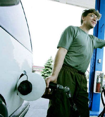 Mike Jorgenson fills up his '97 Chevy Blazer last week in Eagan, Minn., with regular fuel. Jorgenson said he could save big money if he had a flexible-fuel vehicle for his daily 130-mile round-trip commute to work.   (Associated Press / The Spokesman-Review)