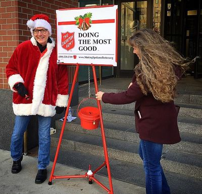 Spokeman-Review editor Rob Curley, dressed as Santa, stands next to a Salvation Army red kettle. (Liz-Anne Kishimoto / The Spokesman-Review)
