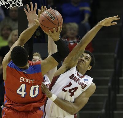 Dayton's Devon Scott attempts a shot against Stanford forward Josh Huestis, right. (Associated Press)
