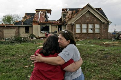 Kim Lane, left, is consoled by her friend Elizabeth Weaver as they stand in front of Lane's house in Murfreesboro, Tenn., which was damaged by a tornado Friday. (Associated Press / The Spokesman-Review)