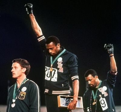 In this Oct. 16, 1968, file photo, Americans Tommie Smith, center, and John Carlos, right, raise their gloved fists in a human rights protest. (STF / Associated Press)