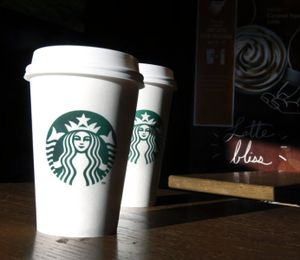 Starbucks cups are shown mugs in a cafe in North Andover, Mass. Starbucks announced today that it was raising prices slightly on brewed coffee, espresso and tea lattes in U.S. company-operated stores. (AP Photo/Elise Amendola, File)