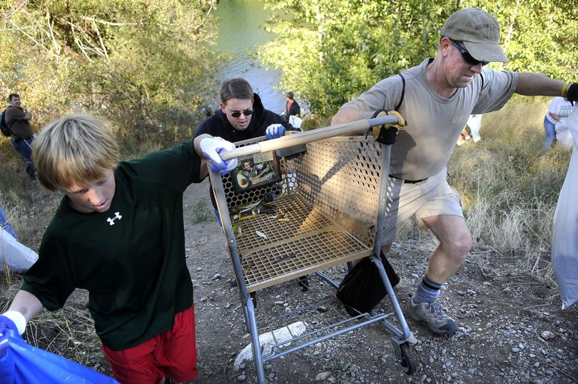 Tyler Zandhuisen, Dave Nelson and Mike Carey drag an old shopping cart from the banks of the Spokane River near Helena and South Riverton during the Seventh Annual Spokane River Clean-up. (Dan Pelle / The Spokesman-Review)