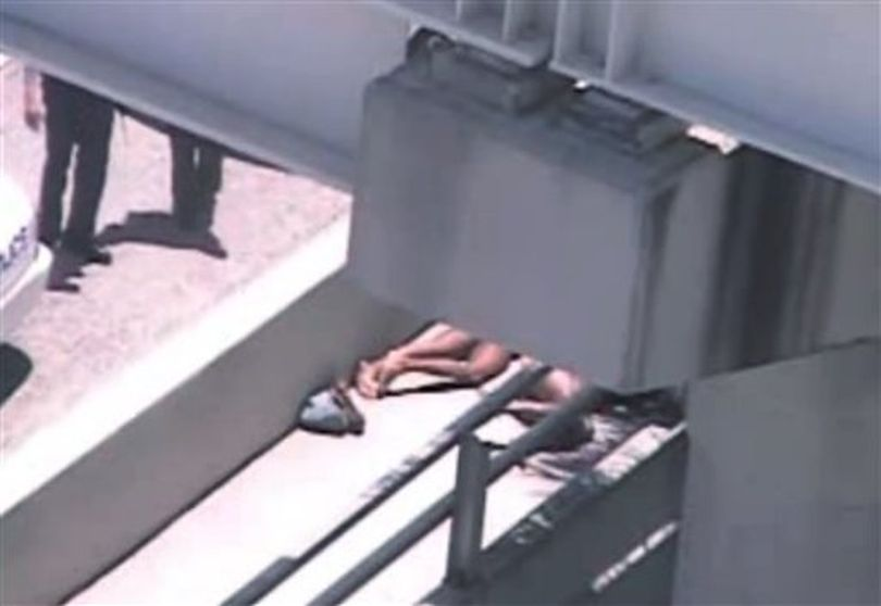 In this image taken from video, Miami police officers stand watch near a naked man, second from right, who was shot dead by a police officer when he refused to stop chewing on the face of the naked man next to him, partially obscured by a railing, on the MacArthur Causeway ramp onto Northeast 13th Street in Miami, Saturday, May 26, 2012. The victim was taken to a nearby hospital. Police say neither man's identity is known. ( (AP Photo/The Miami Herald) )