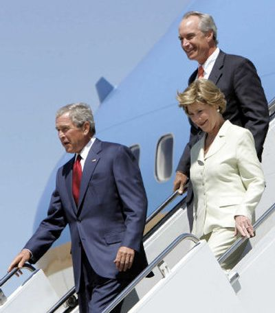 President Bush, first lady Laura Bush and Idaho Gov. Dirk Kempthorne, back, walk down the steps of Air Force One on their arrival at Gowen  Field at the Boise airport on Monday. Bush will spend a couple of days in Idaho before returning to Crawford, Texas.   (Associated Press / The Spokesman-Review)