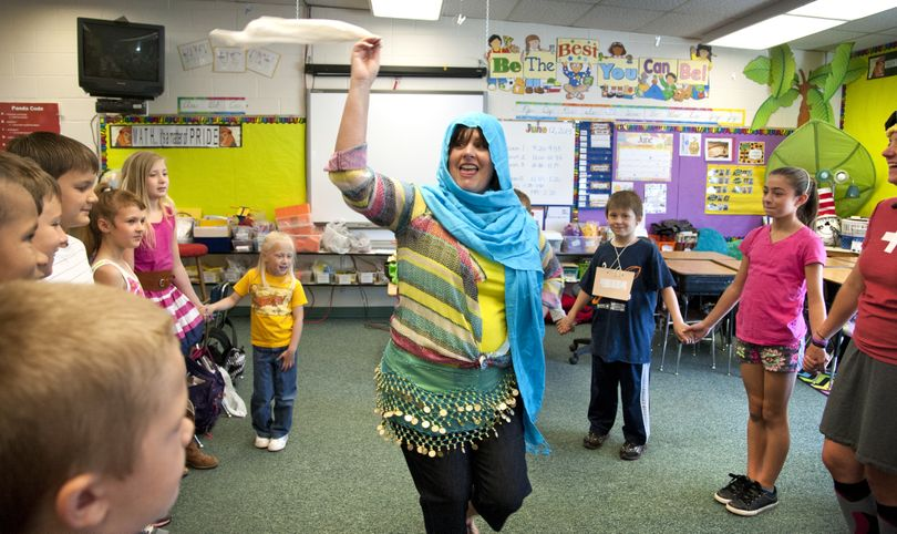 Opportunity Elementary School fourth-grade teacher Laurie Spence and students dance the Dabke, a traditional Lebanese dance, during International Day on Wednesday in Spokane Valley. The five-step dance is often performed at weddings. (Dan Pelle)