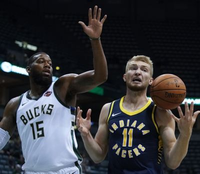 Indiana's Domantas Sabonis and Milwaukee's Greg Monroe go for a rebound during a preseason game. (MORRY GASH / AP)