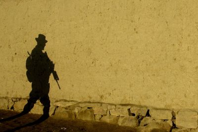 The shadow of a U.S. soldier from the Oklahoma Army National Guard is cast on a wall during a foot patrol at dawn in Hudkhell village on the outskirts of Kabul, Afghanistan.  (File Associated Press / The Spokesman-Review)