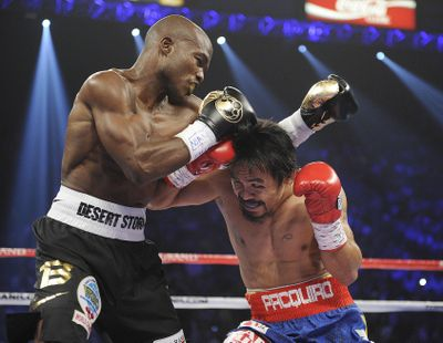 Manny Pacquiao, right, and Timothy Bradley trade blows in the first round of their title fight in Las Vegas. (Associated Press)