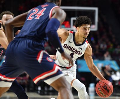 Gonzaga guard Ryan Woolridge drives against Saint Mary's Gaels forward Malik Fitts during the first half of a West Coast Conference championship basketball game in March.  (Tyler Tjomsland / The Spokesman-Review)