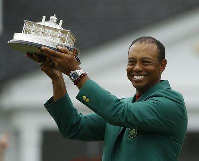 Tiger Woods wears his green jacket holding the winning trophy after the final round for the Masters golf tournament Sunday, April 14, 2019, in Augusta, Ga. (Matt Slocum / Associated Press)