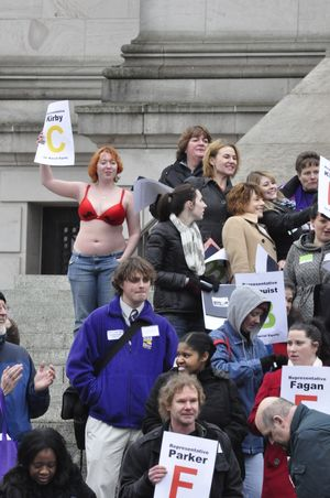 OLYMPIA -- Taylor Malone of Spokane joins protesters on the steps of the state Capitol calling for the Legislature to fund programs to help the poor. She said she took off her shirt to symbolize that with cuts to programs, some people have to make the choice between feeding their familes and buying them clothes (Jim Camden)