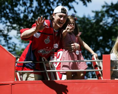 Washington Capitals right wing T.J. Oshie waves while holding his daughter Lyla Oshie during a Stanley Cup NHL hockey victory parade, Tuesday, June 12, 2018, in Washington. (Alex Brandon / Associated Press)