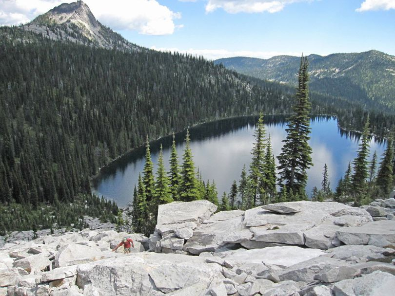 A hiker scrambles up the granite talus above Harrison Lake in the Idaho Selkirk Mountains with Harrison Peak in the background. This popular backcountry destination in the upper Pack River drainage was recommended for wilderness designation by the Forest Service in the 1980s, but the draft management plan released by the Idaho Panhandle National Forests in 2011 does not include this area in wilderness recommendations.  (Idaho Conservation League)