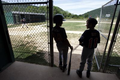 Little Leaguers wait for batting practice. Many preteens play, but numbers fall dramatically by the time they reach their teens.  (File Associated Press / The Spokesman-Review)