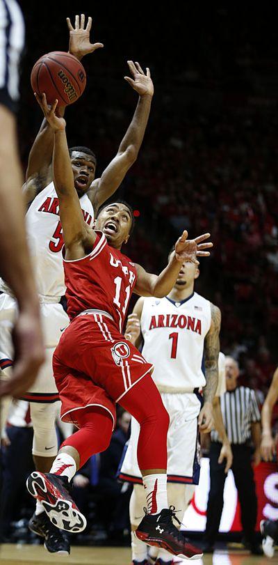 Utah guard Brandon Taylor (center) shoots past Arizona guard Kadeem Allen (left). Taylor scored 19 points during the Utes' 70-64 win Saturday in Salt Lake City. (Associated Press)