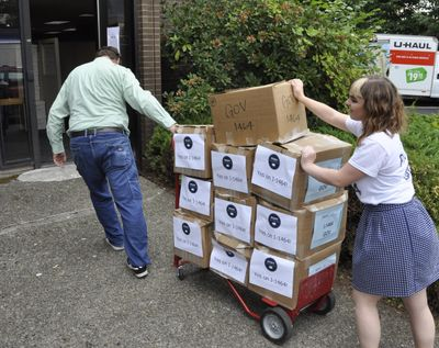 Supporters of I-1464, an initiative that would change some of the state's campaign finance laws and increase government transparency, wheel cartons of signed petitions into the state elections office in Olympia shortly before the deadline on July 8, 2016. (Jim Camden / The Spokesman-Review)