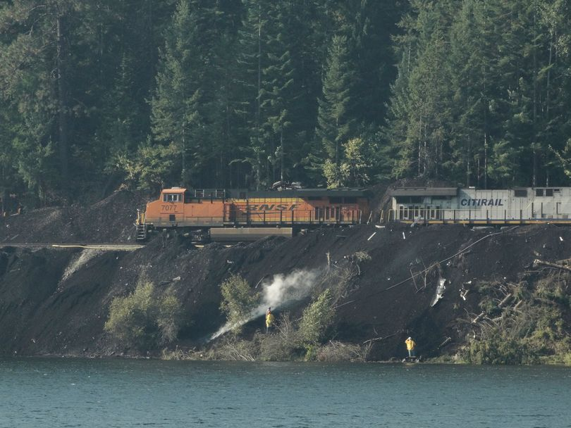On Sept. 16, 2017, Montana Rail Link crews tend to smoldering coal that had spilled along the Clark Fork River during a train derailment in mid-August. The photo was taken in Montana from SR 200 east of the Idaho state line at Milepost 8.  (Sandy Compton)
