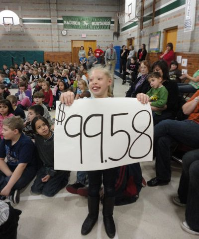 Mia Roberts, a student in teacher Amanda Workman's class at Madison Elementary School, holds up a sign indicating the $99.58 her class raised in a change drive to benefit classmate Snezhana Dedkov.