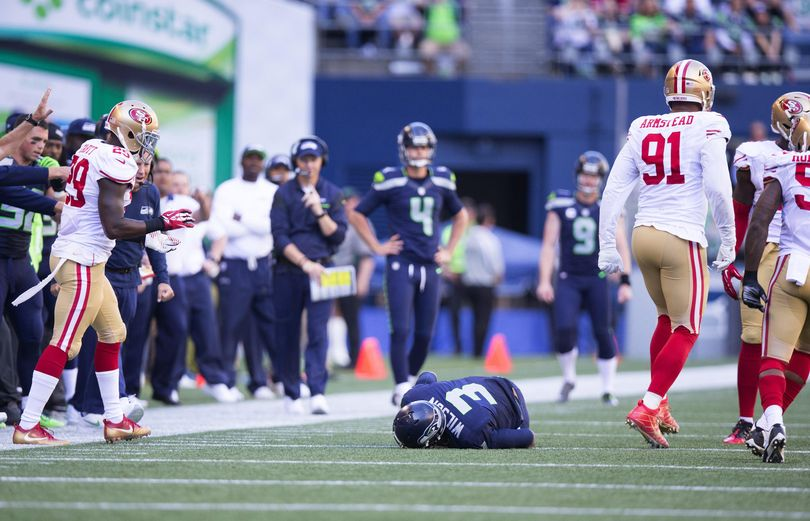 Seattle Seahawks quarterback Russell Wilson stays down after injuring his knee after being tackled by San Francisco 49ers outside linebacker Eli Harold in the second half of the Seahawks' 37-18 win. (Associated Press)