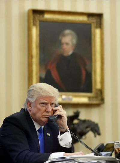 President Donald Trump speaks on the phone in the Oval Office Saturday, with a portrait of Andrew Jackson behind him. (Alex Brandon / AP)
