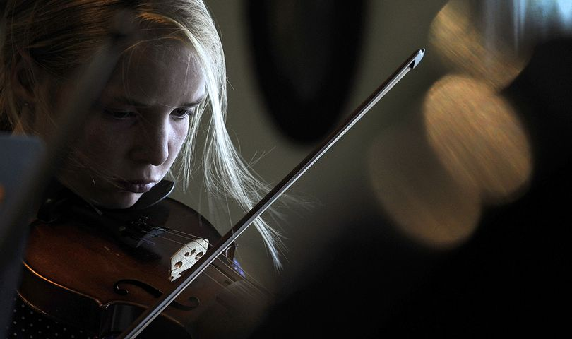 """""""It's challenging,"""" said Nancy Beam, 13, of Rathdrum, as she played her violin during Otis Orchards Strings Camp on Tuesday. (Kathy Plonka)"""