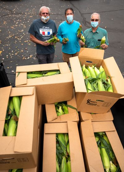 Greater Spokane Rotary Club members, left to right, Daryl Skomer, Chris Baca and Tom Markson wait Wednesday in the parking lot of Darcy's restaurant in Spokane Valley for members to buy fresh-picked corn intended for their food booth at the now-canceled Spokane Interstate Fair.  (Colin Mulvany/THE SPOKESMAN-REVIEW)