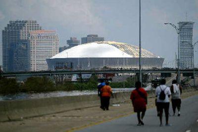 People walk toward the Louisiana Superdome seeking shelter on Wednesday.   (Associated Presss / The Spokesman-Review)