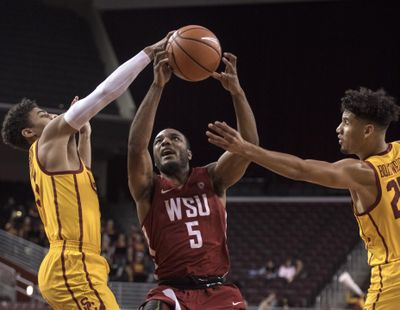 Washington State guard Milan Acquaah, center, goes up for a basket as Southern California guard Derryck Thornton, left, and forward Bennie Boatwright defend during the first half of an NCAA college basketball game Sunday, Dec. 31, 2017, in Los Angeles. (Kyusung Gong / Associated Press)