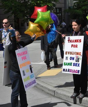 SEATTLE -- Teri McClain, left, and Mary Beth Brotski wear signs thanking President Barack Obama for supporting gay marriage. (Jim Camden)