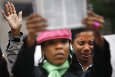 Cynthia Blackledge cries as Brenda Buckner holds up a Bible during a protest of a same-sex marriage bill considered by the District of Columbia Council on Tuesday.  (Associated Press / The Spokesman-Review)