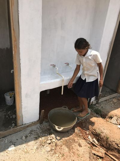 A schoolgirl gets water at hand-washing station built into a new double latrine  in Honduras. Chris Choate, who helped build the facility, has planned another trip to southern Honduras in April to work on a clean water project. (Chris Choate / Courtesy photo)