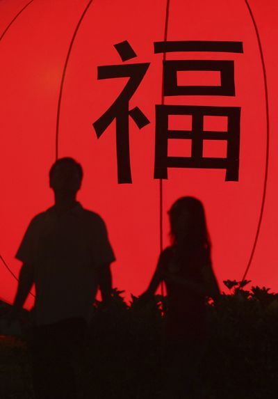 "A couple in Singapore  are silhouetted against a lantern. The character translates to ""fortune.""  (Associated Press / The Spokesman-Review)"
