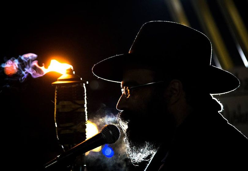 Before lighting a large menorah, Rabbi Yisroel Hahn speaks to the crowd gathered in Riverfront Park on Sunday. The Chabad of Spokane County community center presented the event in celebration of the eight-day Jewish Hanukkah holiday that began on the evening of Dec. 6. (Colin Mulvany / The Spokesman-Review)