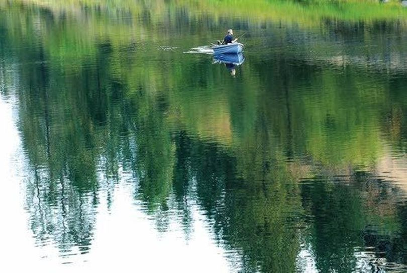 A fisherman gets in some quiet angling on a calm stretch of the Clearwater River above Orofino. (Barry Kough / Lewiston Tribune)