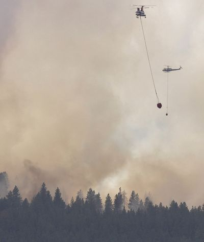 Helicopters drop water Friday afternoon from the Methow River onto a fire near Twisp, Wash. Gov. Jay Inslee was briefed on the fire during a trip he made to talk with local officials about last month's devastating Carlton Complex fires.