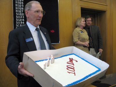 House Assistant Sergeant-at-Arms Al Noyes displays a cake commemorating the 100th day of the legislative session, just after the House rejected the governor's transportation bill.  (BETSY z. RUSSELL / The Spokesman-Review)