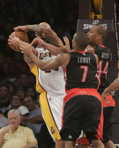 Los Angeles' Robert Sacre, left, battles for a rebound against Toronto's Kyle Lowry and Chuck Hayes in the first half. (Associated Press)
